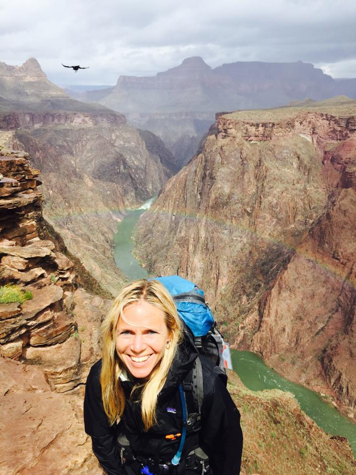 Sara Schulting Kranz in the grand canyon with a rainbow behind her