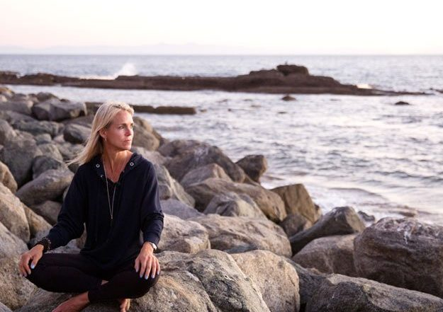 Sara Schulting Kranz on rocks at the shore